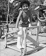 boy holding on to a walker with slanted side rails.