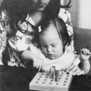 A child removing pegs sitting in an adults lap