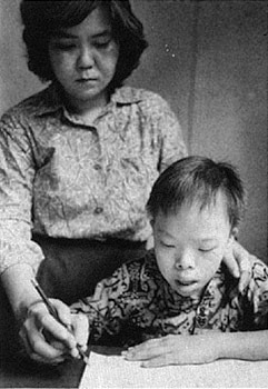 Child learning to write with the guidance of an adult