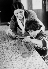 a boy putting pegs in holes while a woman watches.