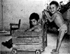 boy using walker to walk with another boy riding in the front compartment.