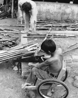 Man standing and boy in wheelchair working with cane.
