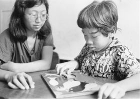 A child solving a puzzle while adult observes