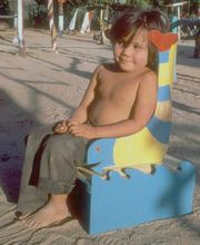 Photo of child in wooden seat.
