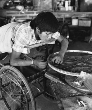 Boy lying face down on board works with bicycle wheels with hands.