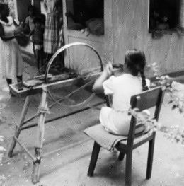 Girl sitting at wheel to make rope.
