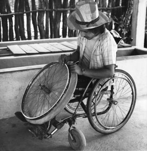 Man in wheelchair working on wheel.