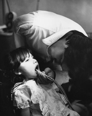 Dental worker with one arm looking into girl's mouth.