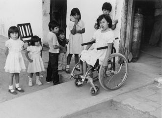 a girl in a wheelchair going down a ramp