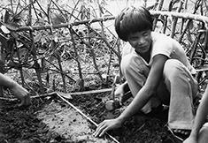 Niño ciego trabajando en un jardín.