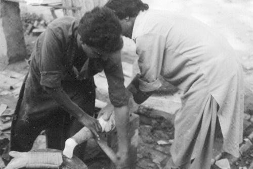 Two workers making plastic leg.