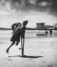a child kicking a ball with his one leg while using a crutch.