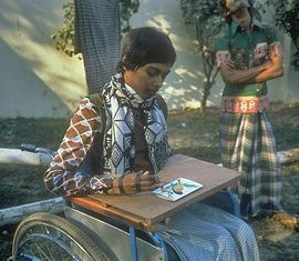 Un joven pintando sobre una silla de ruedas.