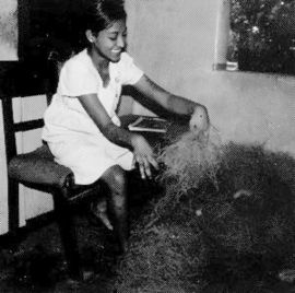 Girl with spastic hands works with plant fiber.