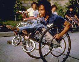 Hombre recargado en una silla de ruedas.