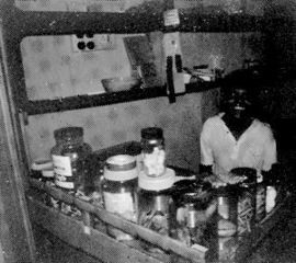 Child behind counter with many jars of things.