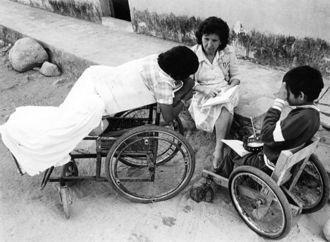 Woman sitting with two children in wheelchairs.