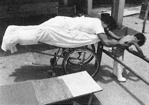 a man lying on belly on a wheel lying cart helping a child walk