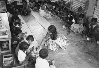 Children in a large circle attended by two women.