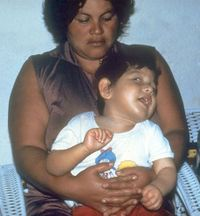A child sitting in an adult's lap