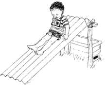 Un niño pequeño con audífonos se resbala en un resbalón.
