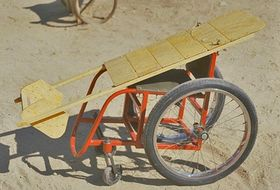 Photo of wheelchair with wooden lying board on top.