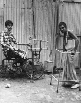 Young man on rudimentary stationary bicycle, young man using walker.