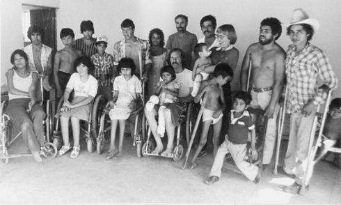 Group of people in wheelchairs, with crutches and standing.