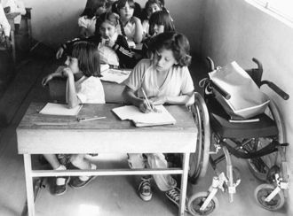 Children seated in rows of desk, one girl sitting at a desk next to wheelchair.