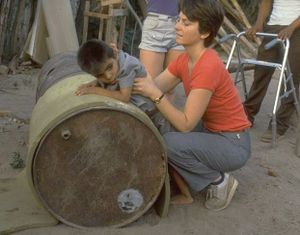 Exercing small child on a horizontally extended barrel.