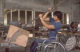 Hombre en silla de ruedas trabajando con una barilla de metal.