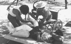 Dos adultos enyesan la pierna de un niño acostado.